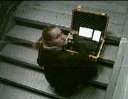 !Mediengruppe Bitnik - Still from Surveillance Chess showing Bitnik sitting with yellow transmission suitcase